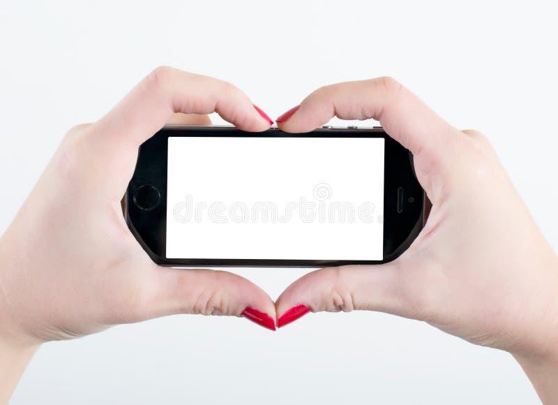 Mains de forme de coeur et écran vide image stock