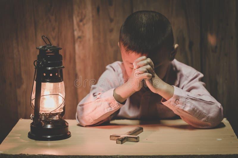 Mains de garçon priant avec une croix sainte dans l'obscurité et avec la lampe à coté, enfant priant pour la religion de Dieu photo libre de droits