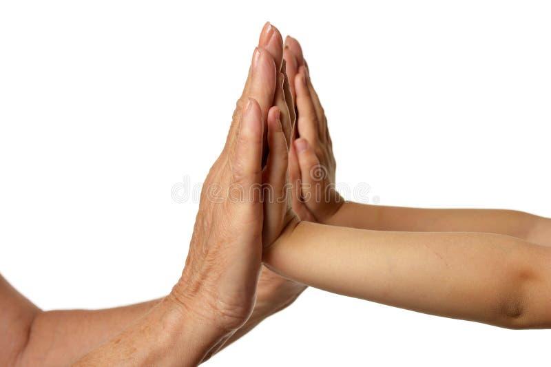Mains de grands-m?res avec des mains de petite fille d'isolement sur le fond blanc image libre de droits