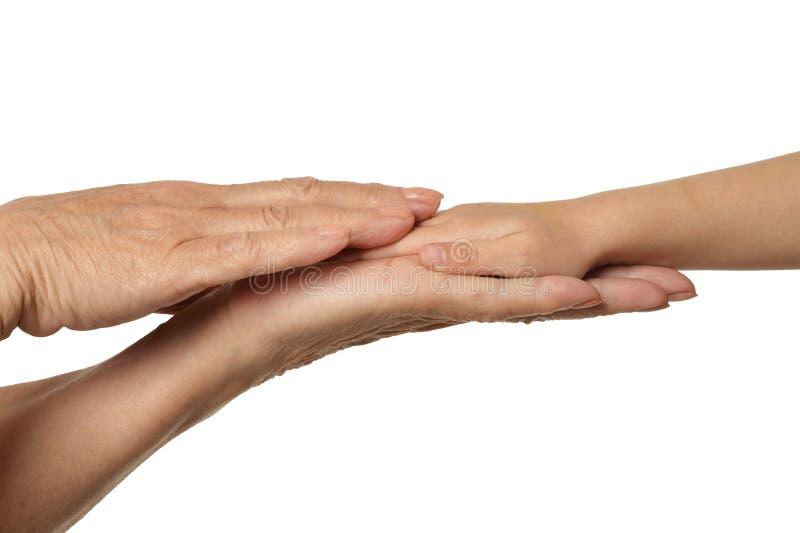 Mains de grands-m?res avec des mains de petite fille d'isolement sur le fond blanc photos stock