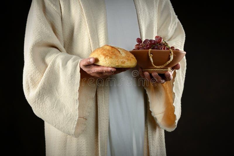 Mains de J?sus retenant le pain et des raisins photographie stock libre de droits