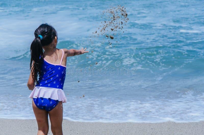 Mains de jeu de petite fille avec le sable image stock