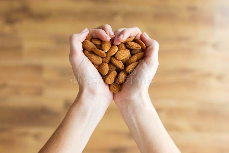 Mains de jeune femme formant la forme de coeur tenant des écrous d'amandes à la maison images stock