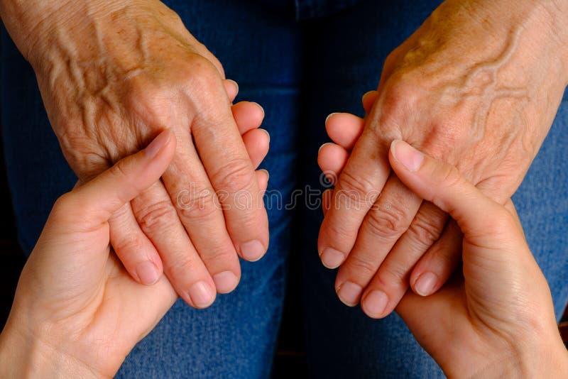 Mains de jeune femme tenant des mains d'une femme agée image stock