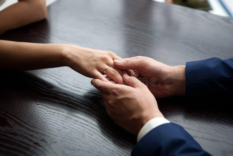 Mains de jeunes mariés image stock