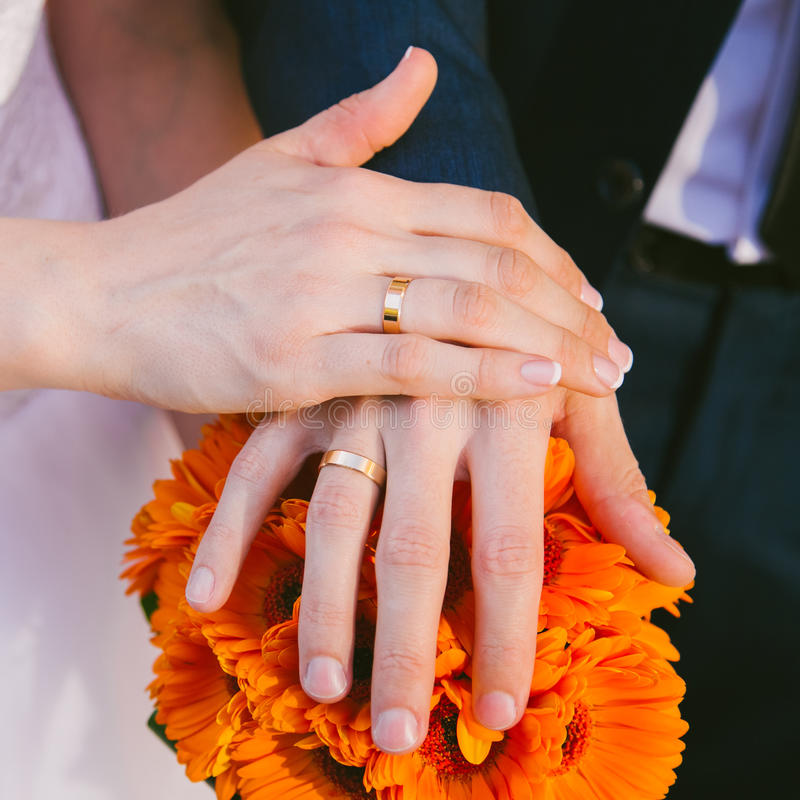 Mains de jeunes mariés avec des anneaux de mariage photo stock