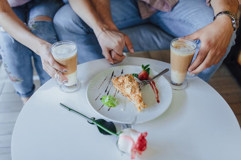 Mains de l'amour dans des couples et un latte photo stock