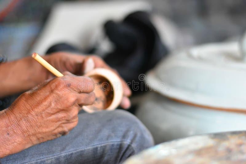 Mains de l'artiste ? l'aide des outils au dessin dans la poterie de terre brune photographie stock libre de droits