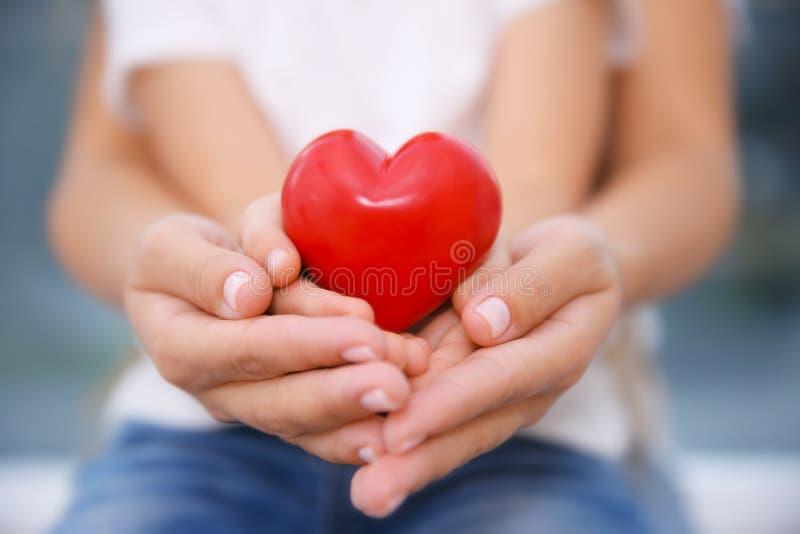 Mains de l'enfant et de la femme adulte tenant le coeur rouge, photos libres de droits