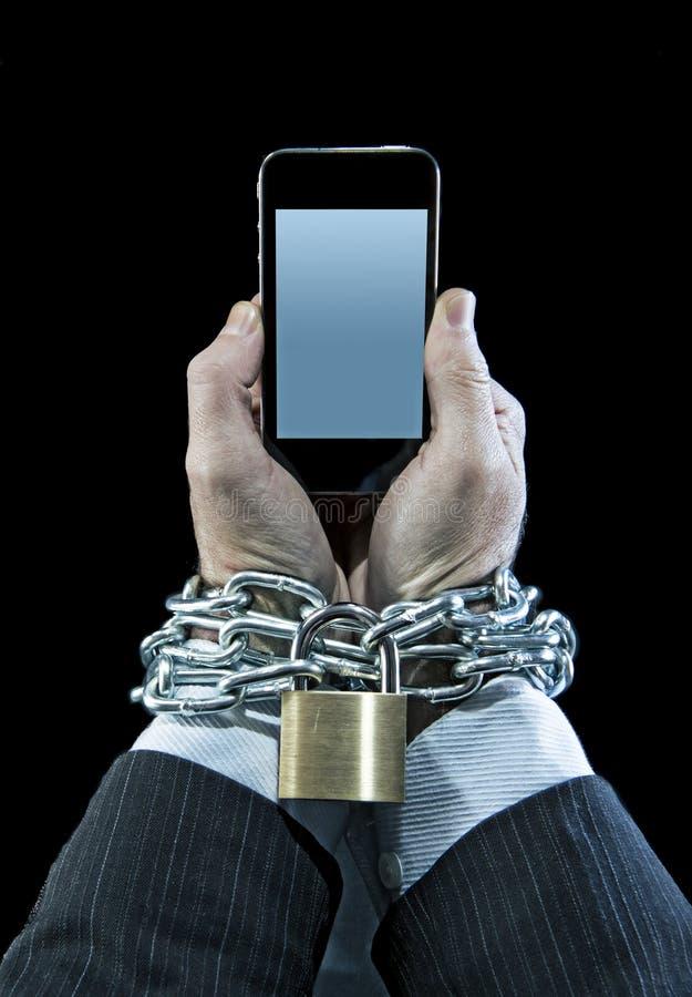 Mains de l'homme d'affaires dépendantes pour travailler verrouillé à chaînes dans la dépendance de téléphone portable photo stock