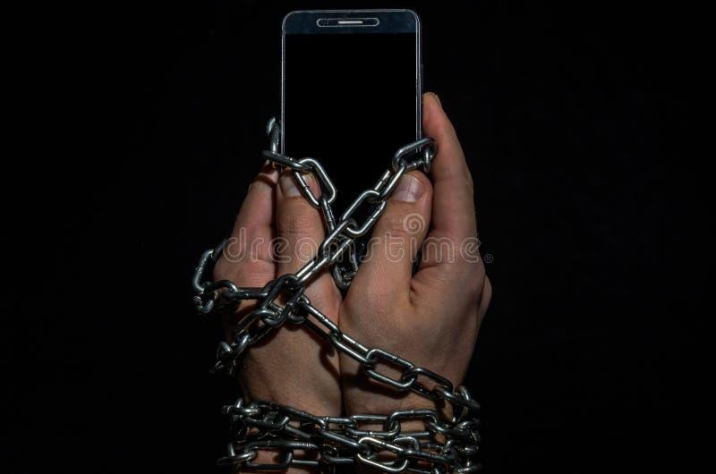 Mains de l'homme enchaînées avec un téléphone portable, un smartphone sur un fond noir photographie stock