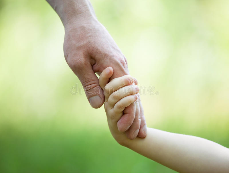 Mains de l'homme et de l'enfant tenant le togethe photographie stock