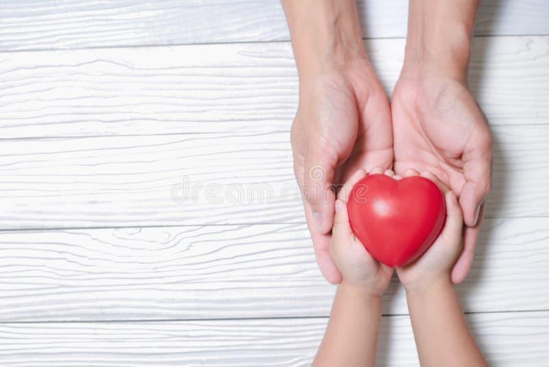 Mains de l'homme et du fils tenant le coeur rouge sur le fond en bois photo libre de droits