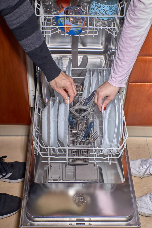 Mains de l'homme et de la femme faisant des travaux du ménage ensemble images stock