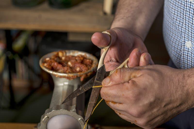 Mains de l'homme faisant le salame photographie stock libre de droits