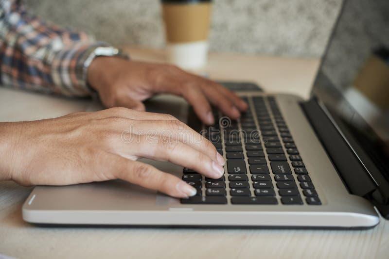 Mains de l'homme travaillant sur l'ordinateur portable images libres de droits