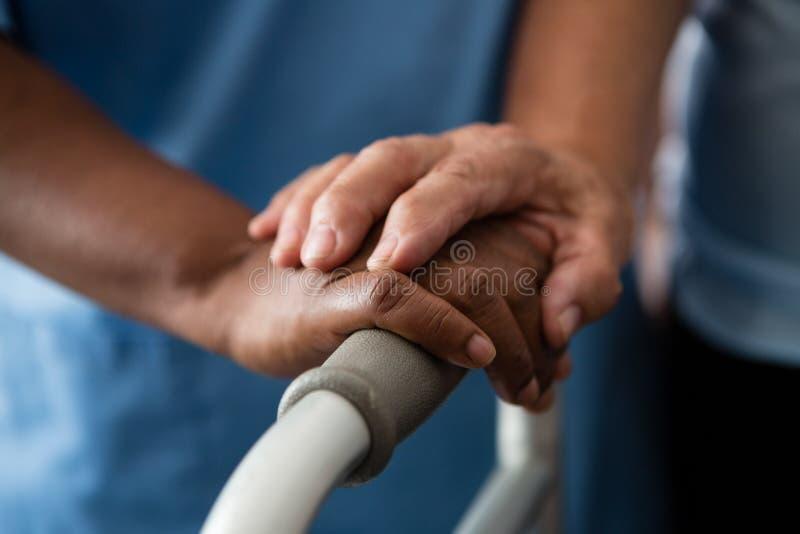 Mains de l'infirmière et de la femme supérieure tenant le marcheur dans la maison de repos image stock
