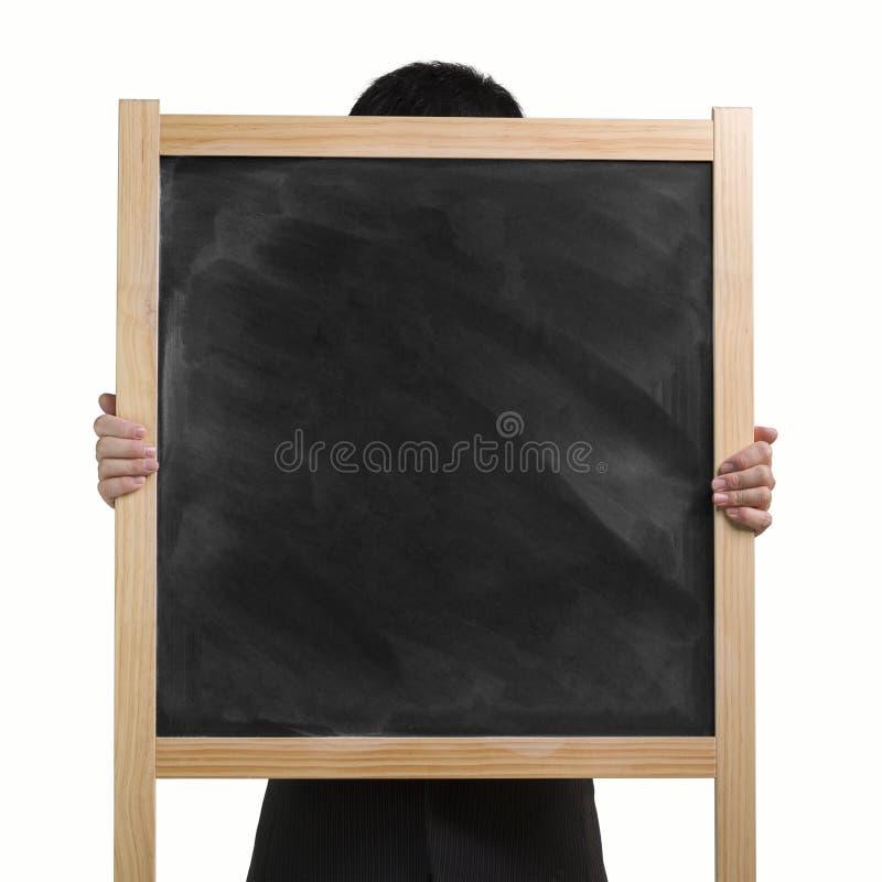 Mains de l'utilisation deux d'homme d'affaires pour soulever le panneau de craie en bois sale dedans photographie stock