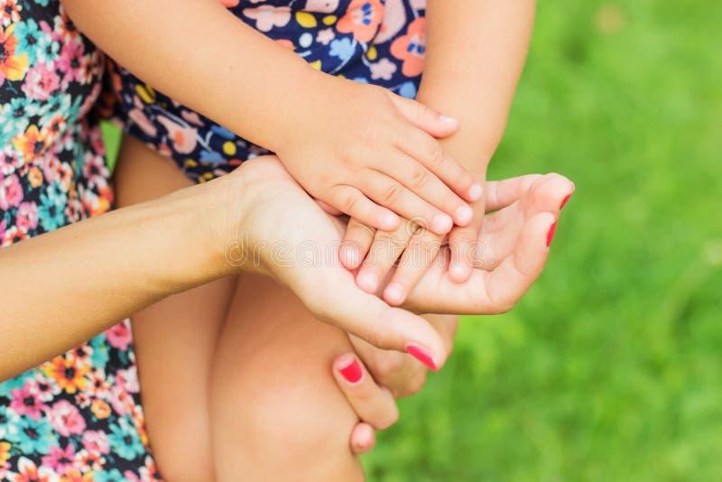 Mains de la fixation de mère et de descendant Stationnement d'été à l'arrière-plan photographie stock libre de droits