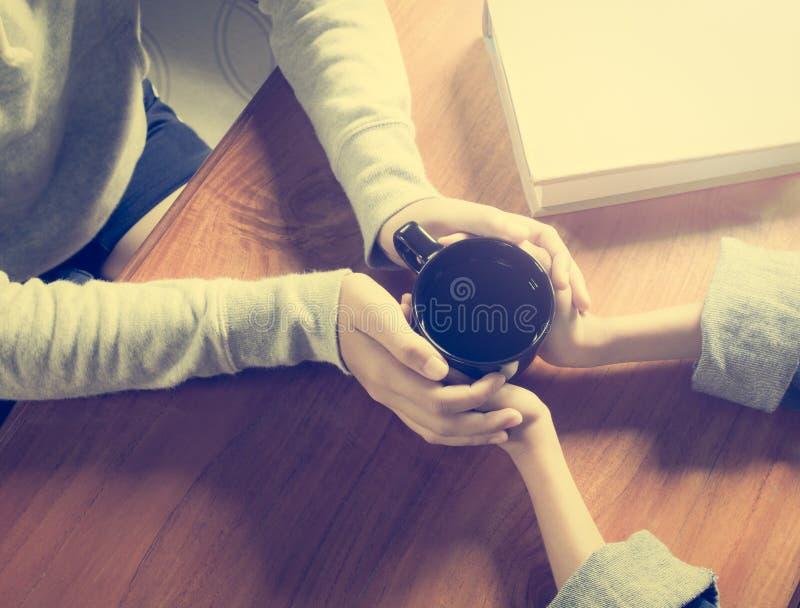 Mains de la mère et de la fille tenant la tasse de café images libres de droits