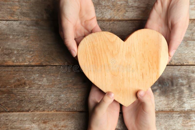 Mains de la mère et de l'enfant tenant le coeur sur le fond en bois images stock