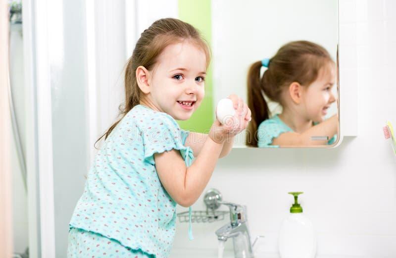 Mains de lavage d'enfant dans la salle de bains photos stock
