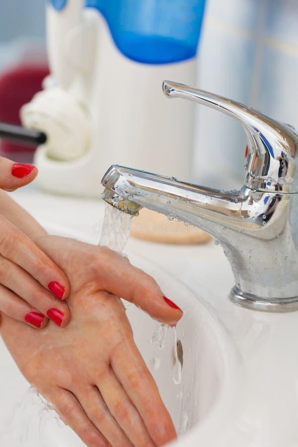 Mains de lavage de femme sous l'eau du robinet débordante dans la salle de bains images libres de droits