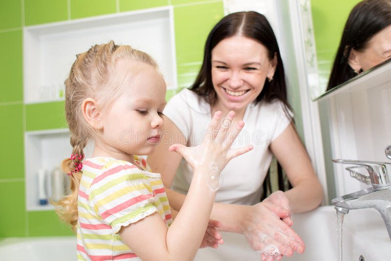 Mains de lavage de fille d'enfant avec du savon dans la salle de bains image libre de droits