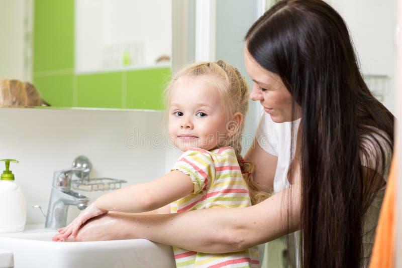 Mains de lavage de fille d'enfant de mère et de fille avec du savon dans la salle de bains image stock