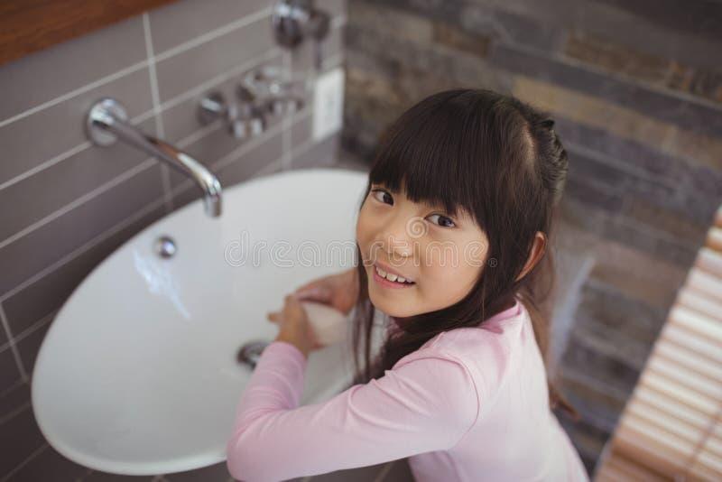 Mains de lavage de fille dans l'évier de salle de bains image stock
