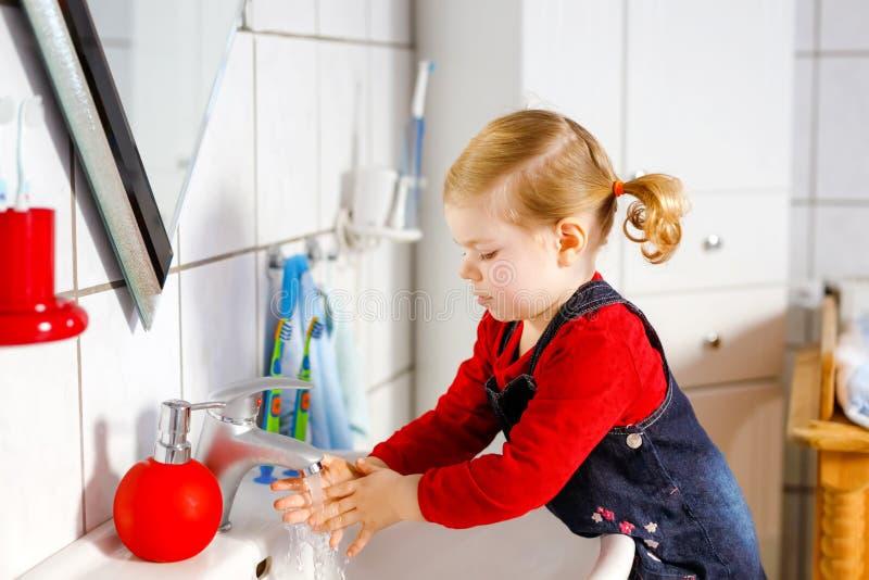 Mains de lavage de petite fille mignonne d'enfant en bas âge avec de l'eau le savon et dans la salle de bains Enfant adorable app photographie stock libre de droits