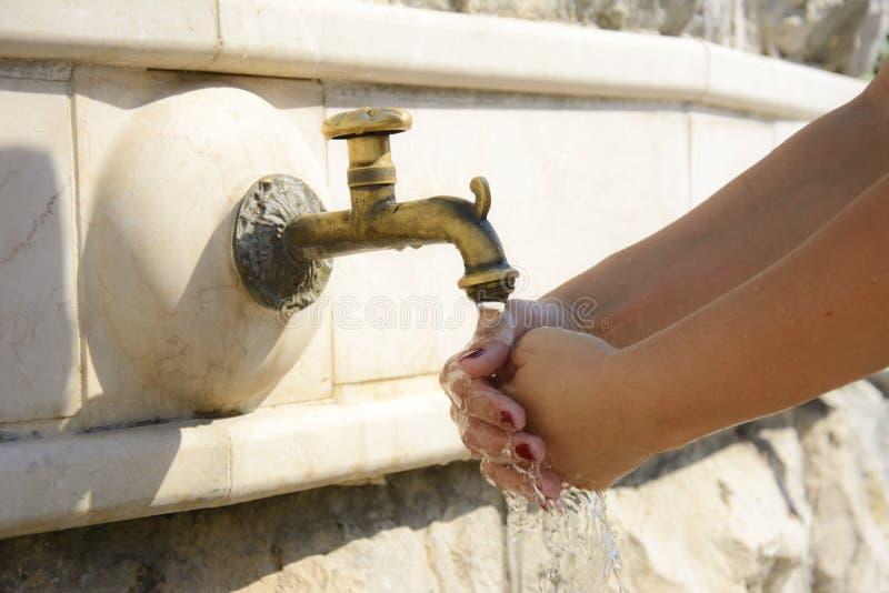 Mains de lavage sur la fontaine de robinet photos stock