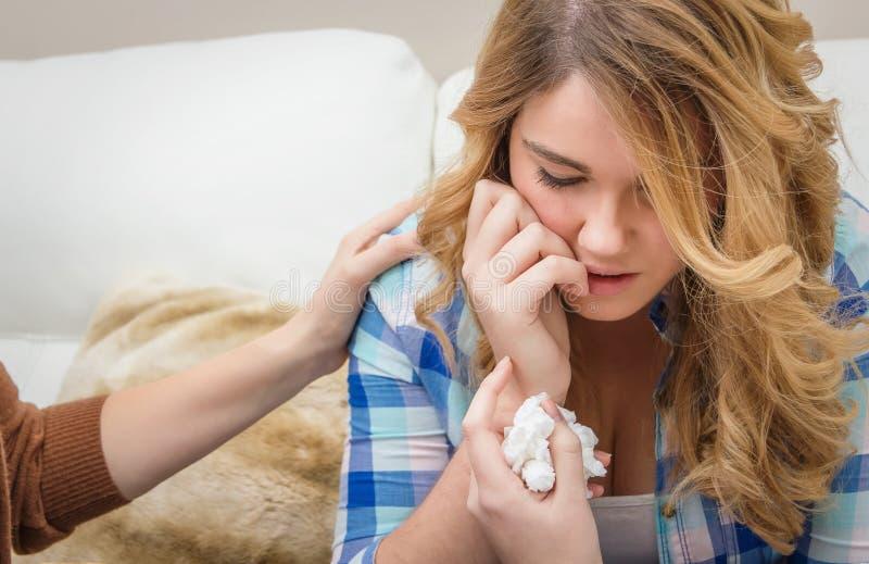 Mains de mère consolant pleurer de l'adolescence triste de fille images stock