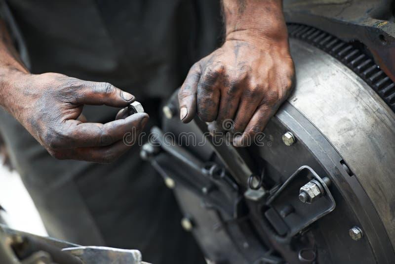 Mains de mécanicien automatique au travail de réparation de véhicule images libres de droits