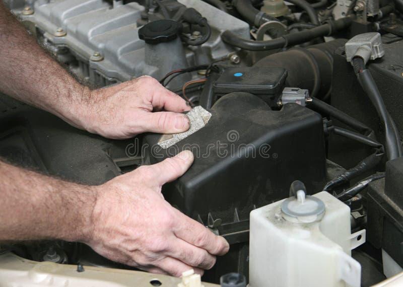 Mains de mécanicien sur le cache de filtre photos stock