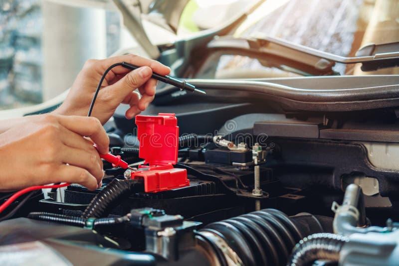 Mains de mécanicien de voiture fonctionnant dans le service des réparations automatique photographie stock