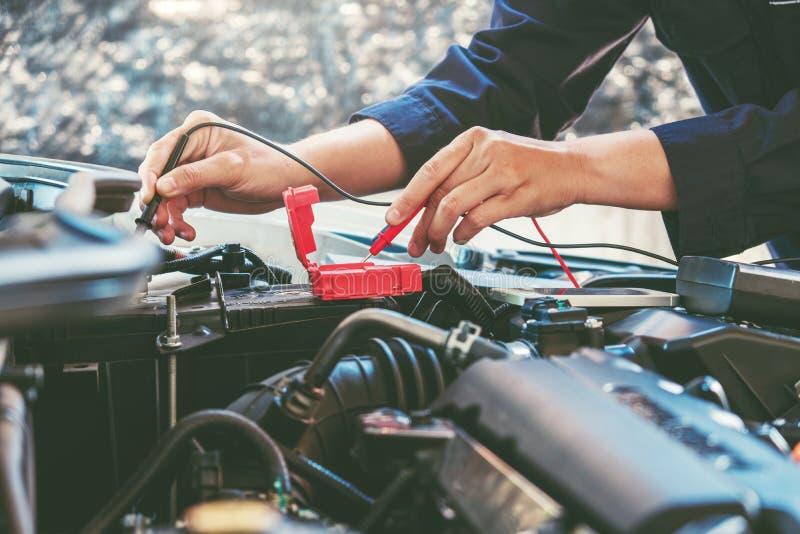 Mains de mécanicien de voiture fonctionnant dans le service des réparations automatique images stock