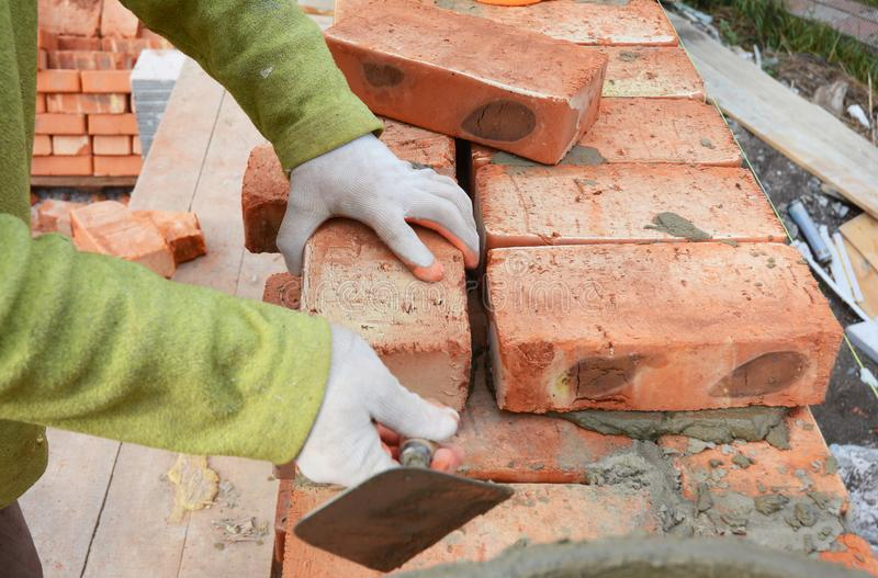 Mains de maçons dans la maçonnerie de gants de maçonnerie sur le chantier de construction de Chambre Maçonnerie, brique image stock
