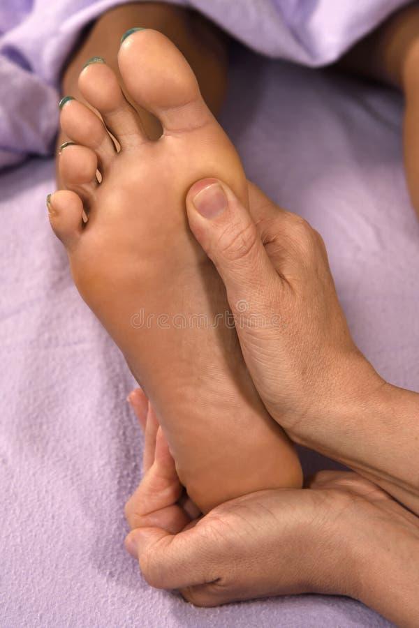 Mains de massage de pied de réflexothérapie dessus à la station thermale de jour photographie stock libre de droits
