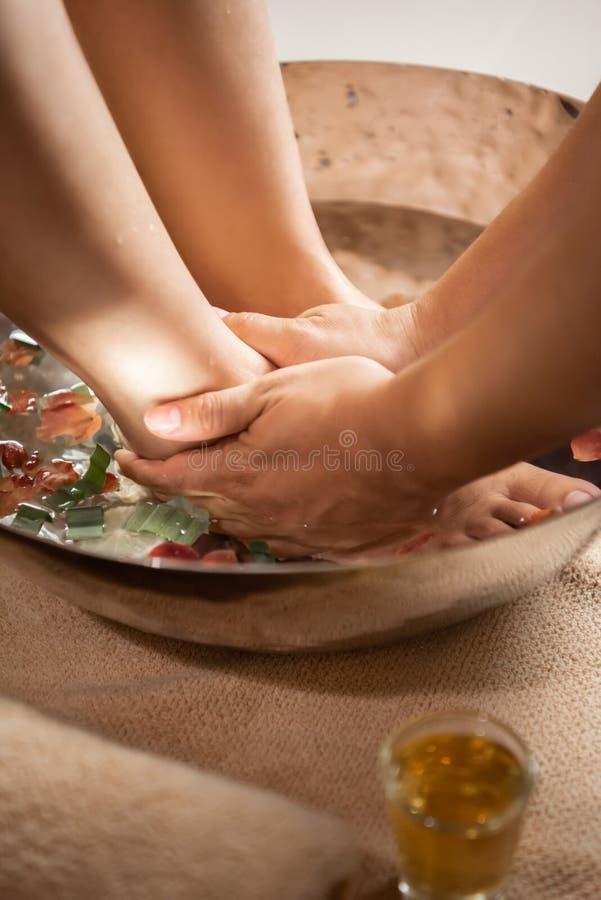 Mains de masseuse lavant le pied femelle à la station thermale photographie stock