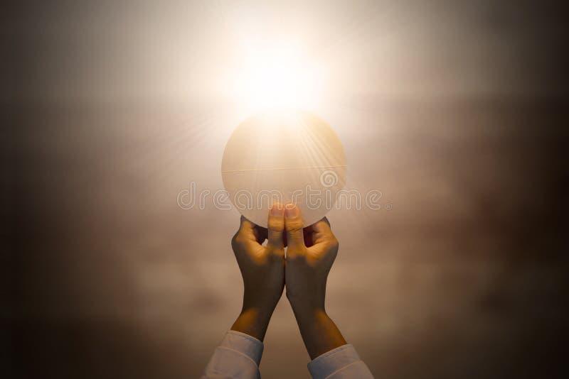 Mains de pasteur tenant une gaufrette lumineuse de communion photos libres de droits