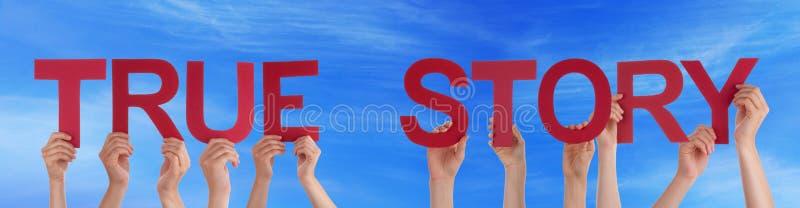 Mains de personnes tenant le ciel bleu histoire droite rouge de Word de véritable image stock