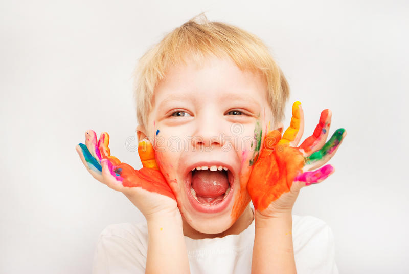Mains de petit garçon peintes en peintures colorées photos stock