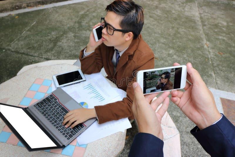 Mains de photographe prenant une photo de jeune homme beau d'affaires tout en parlant au téléphone avec son smartphone image stock