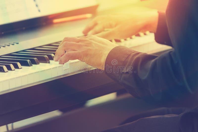 Mains de pianiste jouant le piano dans un concert extérieur avec la fusée du soleil images stock