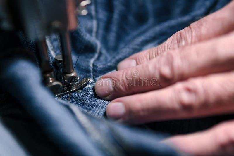 Mains de plan rapproché d'homme de tailleur travaillant à la vieille machine à coudre textile de tissu de tissu de jeans dans le  images stock