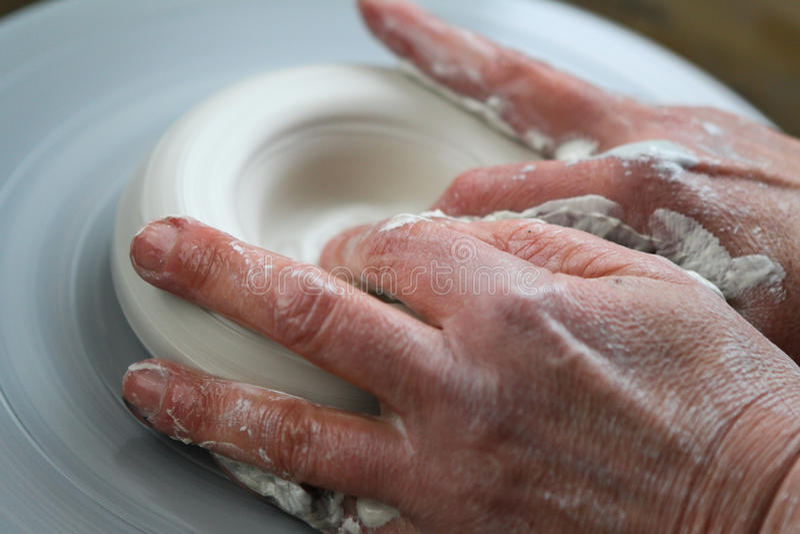 Mains de potier créant en céramique sur le cercle photo stock
