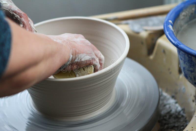 Mains de potier créant en céramique sur le cercle photo libre de droits