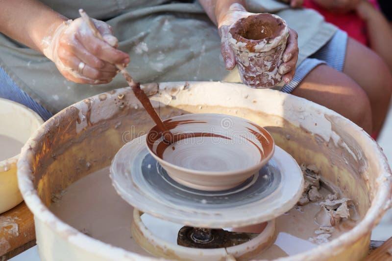 Mains de potier, créant un pot de terre sur le cercle, plan rapproché images libres de droits