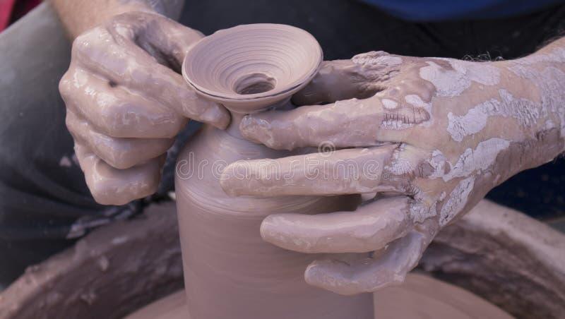 Mains de potiers couvertes en argile formant un pot sur une fin de roue  images libres de droits